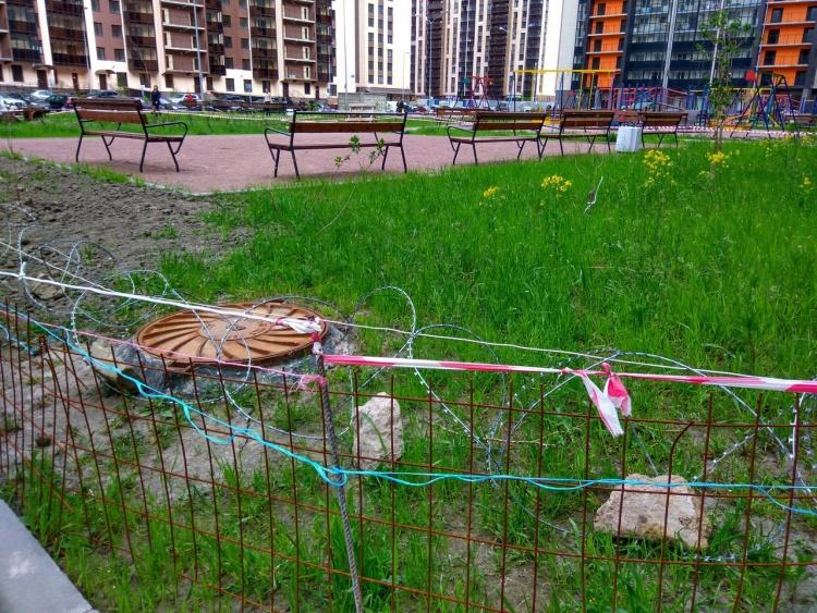 В Мурино газон у детской площадки оградили колючей проволокой